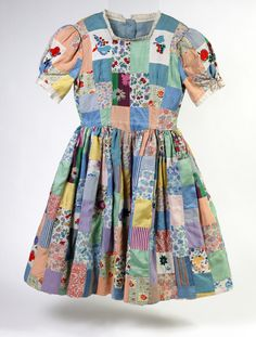 Girl's patchwork dress, English, 1944. Made for a little girl named Jane after an unexpected invitation to a children's party. By this stage of WWII, parties were unusual due to major food shortages, and many children had been separated from family and friends. New party dresses were difficult to obtain as clothing was rationed. The night before the party, after Jane had gone to bed, her mother collected every spare scrap of fabric she could find. In the morning, Jane's party dress was ready.