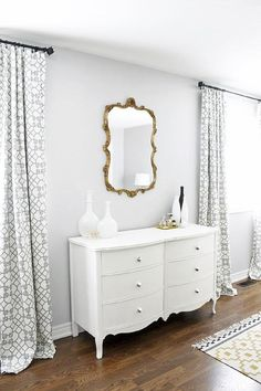 Master Bedroom, West Elm Shane Powers Opal Vases, silver gray paint color, Gold leaf scroll mirror, white French dresser, Windsor Smith Pelagos drapes.