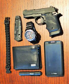 My EDC (Everyday Carry). Contents: Cell phone - Verizon Razr MAXX HD, Wallet - Relic Durham Traveler, Flashlight - Stremlight Microlight 1A, Watch - Citizen Eco Drive Sky Hawk, Folding Knife - Benchmade mini Barrage, CCW - Sig Sauer P938 (all black with extended magazine for pinkie grip), Bracelet - made with 9' of black paracord  .