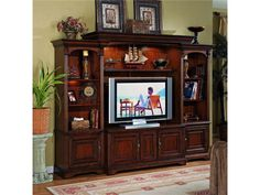Display your new Plasma/DLP/LCD TV with this entertainment center creating a bold focal point to a room while adding functional storage solutions.  This six piece entertainment center features a center console offering two outside doors with interchangeable wood/glass panels, one adjustable shelf behind each door; center door with touch latch and interchangeable wood/speaker cloth panels, one adjustable shelf behind door and three electrical outlets.  The left and right pi...