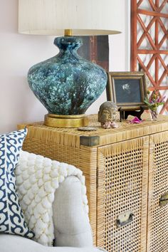 A table lamp atop a rattan cabinet in a living room. Tami Ramsay, Lonny October issue