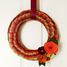 Ring in the crisp temperatures and warm colors of Halloween with a new decoration at your front door or over your fireplace. This autumn beauty captures the glorious shades of turning leaves with plaid ribbon and fabulous wool-felt blooms. Start with a straw wreath and 2-inch-wide plaid ribbon in harvest colors. Hot-glue a ribbon end to the back of the wreath. Wrap ribbon around the wreath; glue the other end of the ribbon to the back. Add other rolls, if necessary, in the same manner until…