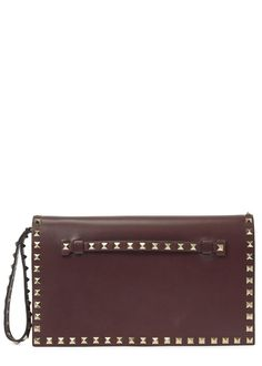 Valentino�bordeaux�leather clutch Wrist strap, rockstud trims, designer stamp, studded slip tab at front, three internal compartment, zip fastening internal pocket Concealed magnetic fastening at flap front Comes with a dust bag