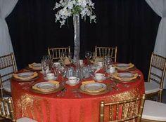Gold chivari chairs with orange crush table cloth.