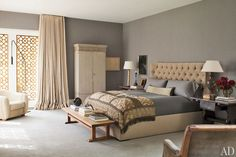 upholstered bed, taupe bedroom, grey sheets, bench, blanket, curtains, wood side table