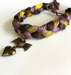 Purple and gold braided friendship bracelet heart by BeadingByJenn, $7.50 #jewelry #bracelet #friendshipbracelet #braidedbracelet #purple #gold #beadingbyjenn #handmadejewelry #accessories #backtoschool #teenfashion #heart #bow #girls #womens #fashion #etsy