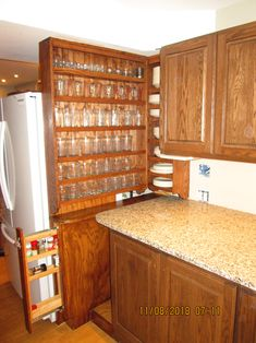 The base cabinet pullout spice rack (open), has a bottle cap opener for a handle. The tall cabinet end panel and the base cabinet end panel were also left over from a previous kitchen remodel. They were re-stained using the Minwax English Chestnut stain, so they all match the upper and lower kitchen cabinets factory stain. The two open shelf cabinets were stained to match, when they were built by Midwest Classic Furniture and Crafts, as a special order.