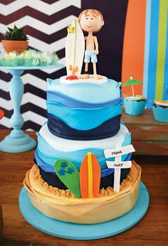 A Surfing Birthday Party with octopus & seashell brigadeiros, chocolate sand pails, drink umbrella topped cupcakes, surfing cake + shark fin topped jars