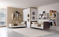 Este es el dormitorio de los niños. Hay dos camas, dos estanterías con algunos libros y varios objectos y un grande armario con dos espejos redondos. Hay tambièn una alfombra blanca.