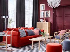 Séjour en gris et rouge foncé, avec canapé orange, tapis à rayures et fauteuil en rotin. Canapé STOCKHOLM