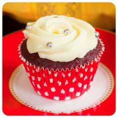 Cupcake Red Velvet - PARA A MASSA: 280 gramas (1 e 1/2 xícara) de AÇÚCAR CRISTAL 240 gramas (1 e 3/4 xícara) de FARINHA DE TRIGO 20 gramas (1/4 xícara) de CACAU 100% 1 pitada de SAL 2 gramas (1/2 colher de chá) de FERMENTO EM PÓ 2 OVOS 120 gramas de MANTEIGA SEM SAL 100 ml de ÁGUA 150 gramas de IOGURTE NATURAL 12 gramas de CORANTE EM PÓ VERMELHO VIVO 6 gramas (1 colher de chá) de BICARBONATO DE SÓDIO 2 colheres de sopa de VINAGRE 1 colher de sopa de EXTRATO DE BAUNILHA