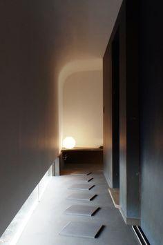 廊下の天井は包み込むように大きくカーブしている。右の壁は濃紺の和紙(壁紙)が貼られ光を吸収している。 地窓からは外構の植栽が覗き、床に飛び石を配することで外の雰囲気を演出している。また飛び石はこのほの暗い空間に距離感を与えてくれる。japan-architects.com
