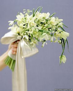 The graceful quality of fritillaria and miniature cymbidium orchids enhances this bouquet's flowing composition, while lily-of-the-valley is sprinkled throughout like droplets. Accents of green -- in the foliage and on the tips of snowdrop petals -- punctuate the vision of soft white. A single dangling fritillaria adds charm; the silver metallic bow, elegance.