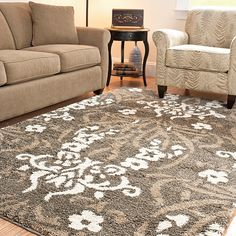 Accentuate your living space with this power-loomed shag area rug. The contemporary rug features a smoke-colored background and with a modern floral design in shades of grey and white. The generous one-inch pile height makes walking on it comfortable.