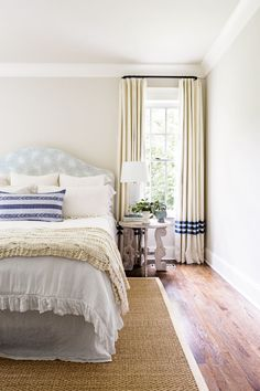 The master bedroom is infused with a subtle bit of pattern play. Anchoring the look is a shapely block-print upholstered headboard paired with an indigo pillow and a creamy cable-knit throw.
