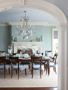 Viewed through the elliptical arch at the entry hall, the dining room has a classically designed fireplace and ceiling cornice.