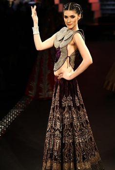 The use of velvet always creates a masterpiece. Beautiful colour combination and stunning detailing on the skirt. The blouse is unique, full work yet looks so classy. Anamika Khanna