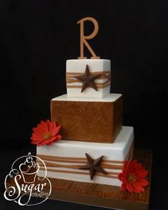 Rustic western wedding cake with gerberas and Texas stars. Monogram is hand-cut, gumpaste daisies & tooled leather, fondant on the base board.