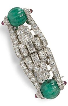 Art Deco Platinum, Carved Emerald, and Diamond Dress Clips, each set with a gadrooned emerald bead with cabochon ruby terminals, and transitional-, old single-, and baguette-cut diamonds, with fitting for brooch conversion, unsigned, in a Cartier box. #ArtDeco #DressClips