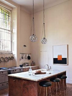 minimal kitchen with faceted globe pendants/ wood island  Rose Uniacke