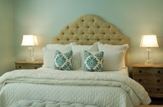 Benjamin Moore Woodlawn Blue was the perfect paint color behind this linen tufted headboard.  Simple white bedding and turquoise throw pillows create a serene feel for this master bedroom.
