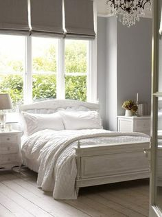 White and grey with bed backed up against the window...