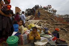 People sit With their belongings outside a damaged temple in