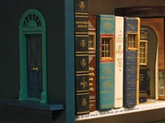 """Fairy door in side of bookshelf leading to a """"fairy house"""" out of classic novels. Lights turn on and off when fairies are home! This would be a great nightlight idea for the top shelf of the bookcase! From the Ann Arbor District Library! Fairy Land, Fairy Tales, Kobold, Fairy Doors, Library Displays, Ann Arbor, Book Nooks, Fairy Houses, Faeries"""