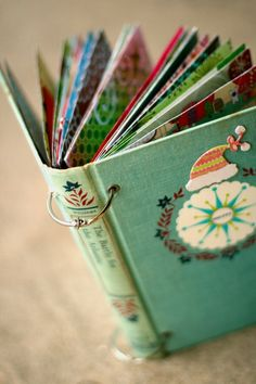 "December Daily 2009 - Two Peas in a Bucket-make a scrapbook with the cover of an old book. Add eyelets and then put book rings thru them to ""bind"" the pages."