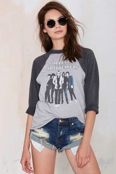 This vintage Tom Petty tee is heather gray and features charcoal gray raglan sleeves, band graphic at front, loose fit, and curved hemline.