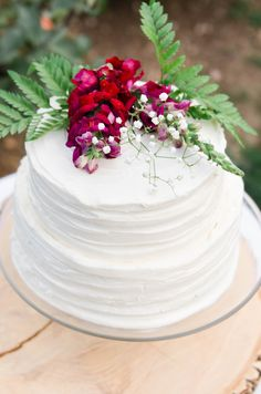 Thick white frosting, bright red floral cake topper, small two-tier wedding cake // Kaytlin Lane Photography
