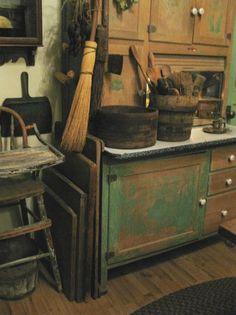 The green Sellers cupboard, with one stack of dough boards leaning against it and the old sage green paint high chair.