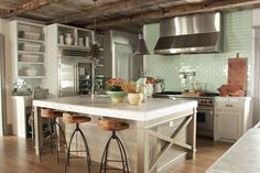 Wood floors, creamy/gray cabinets, white countertops, and soft green accents