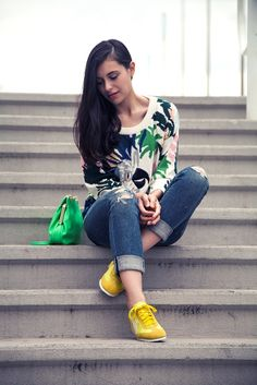 With printed sweatshirt, cuffed jeans and green bag