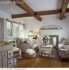 kitchen, neutral colors, shabby chic, light tan sofas, salvaged architectural accents, fireplace with wood shutters, white roses, wood floors, coffered beam ceiling, country modern, simple swag , antiques, distressed furniture