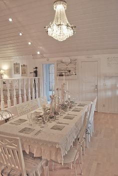 Beautiful table setting. White washed wood panelled wall and ceiling.
