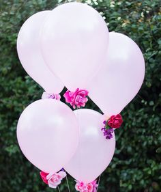 Dress up plain balloons with fake flowers for an extra romantic touch. Clip the stems off the fake flowers and glue to inflated balloons. Then add twine in a coordinating color to the end of the balloon. Place them on dining chairs if you're hosting a dinner (everyone can take a balloon home) or display a grouping in the corner of a room.