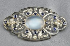 14kt White Gold, Moonstone, Sapphire, Seed Pearl, and Diamond Brooch, set with a cabochon moonstone measuring approx. 17.20 x 14.00 x 6.90 mm, further set with circular-cut sapphires and old European- and single-cut diamonds, seed pearl accents. Undated but assumed to be Edwardian or Edwardian style
