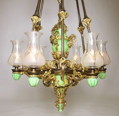 A Very Fine and Large English 19th Century Porcelain, Ormolu and Silvered Bronze Six Light Gasolier Chandelier Messenger & Sons, Birmingham, England (now electrified). The impressive suspending frame with six scrolling foliate-cast rods in a two-tone finish with silvered and gilt-bronze mounts in the form of flowers, the center bowl-shaped body surmounted by a baluster three-handled vase with figures of Putti, all issuing six straight arms, each with its original hurricane glass shades…