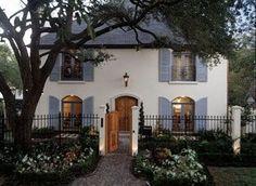 cream exterior, teal shutters, wood door