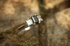 Palladium engagement ring with emerald cut black diamond centre stone and two adjacent princess cut diamonds.
