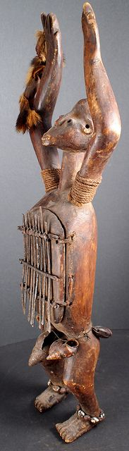 Figurative Likembe, Sanza, Thumb Piano, Azande people, DRC- This little instrument is known by many names including Likembe, Mbira, Sanza and Thumb Piano. It was carved by the Azande people in Northern DRC.  Thumb Pianos are a traditional African musical instrument which take many forms and are used in many different cultures across Africa.  This one is a female figure adorned with shells small amulets, a fibre cord, and a small piece of animal skin representing a dance whisk. The keys…