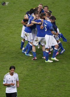 Germany's Khedira leaves the pitch as Italy's players celebrate wininng their Euro 2012 semi-final soccer match at the National Stadium in Warsaw. LEONHARD FOEGER/REUTERS