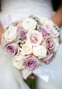 What a gorgeous wedding bouquet! Pink and purple roses accented by tiny crystals. As a floral designer myself this is the first bouquet that really caught my attention that I would want for my own wedding.