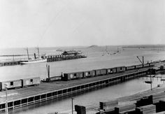 (ca. 1898)* - View shows San Pedro Harbor and Terminal R.R. Depot. Stacks of lumber can be seen in the foreground. Deadman's Island and breakwaters is in the background.