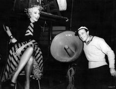 """Dolores Gray and Gene Kelly listen to a playback on the set of """"It's Always Fair Weather"""""""