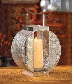 This stunning pillar candle lantern features elaborate carving on either side of the candle holder, and the squared base and handle are the perfect geometric accent for this lantern's rounded beauty.