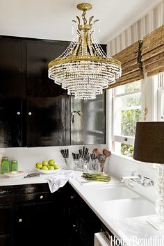 shiny black cabinets, white counters and bamboo blinds! plus a glitzy chandelier add some glamour to your kitchen