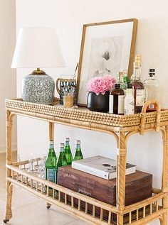 This gorgeous rattan bar cart is enlivenedwith a repurposed vintage ginger-jar lamp and a print byRon van Dongen.