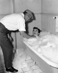 Director Billy Wilder appears to arrange bubbles around Tony Curtis during production on SOME LIKE IT HOT, 1959.
